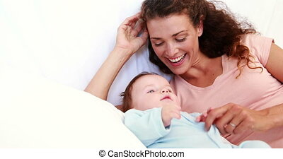 Baby boy in blue babygro being tickled by mother at home in...