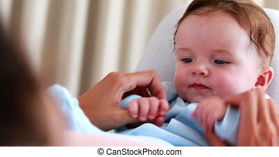 Baby boy in blue babygro playing with mother at home in...