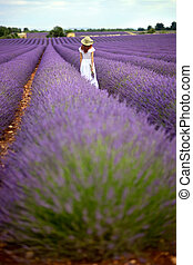 Young romantic lady in white dress and hat walking in violet...
