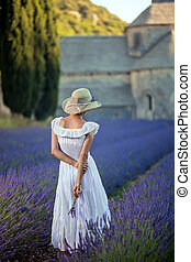 Romantic lady in lavender field. An ancient monastry in...
