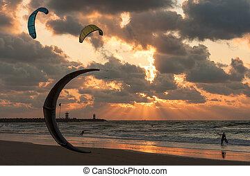 Kite surfing in the sunset at the beach of Scheveningen, the...