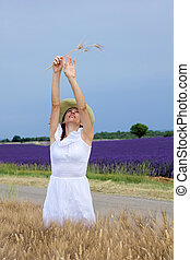 Happy young woman in white dress standing in cornfield. -...