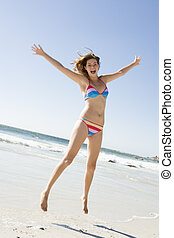 Woman leaping on beach - Woman wearing bikini leaping on...