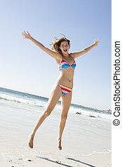 Woman leaping on beach - Woman wearing bikini leaping on...