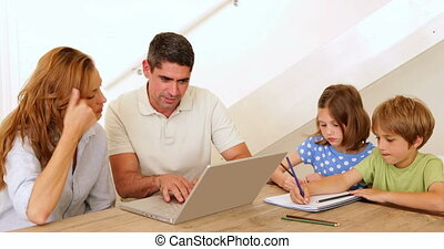 Parents using laptop and children colouring at the table at...