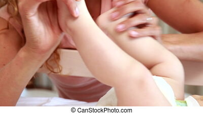 Smiling mother playing with baby sons feet in his crib at...