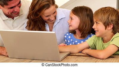 Smiling family using laptop together at table at home in...