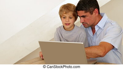 Little boy using laptop with his father