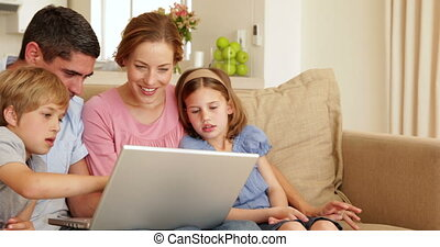 Happy young family sitting on the sofa using laptop together...