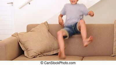 Little boy jumping down on the sofa at home in living room