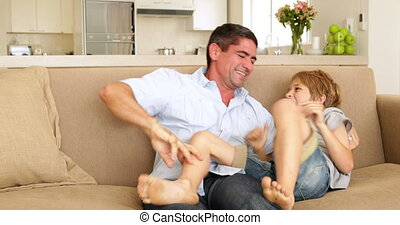 Father and daughter tickling brother