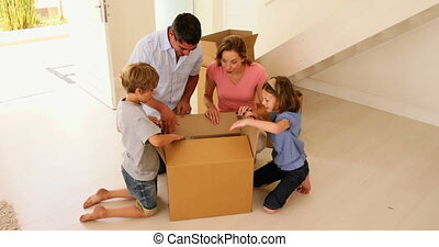 Happy family opening box in their new home in their new home