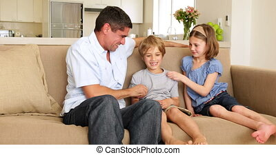 Father and daughter tickling son