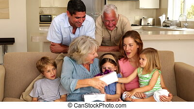 Grandmother getting presents from her grandchildren on couch...