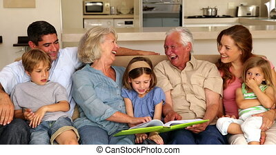 Extended family looking at photo album together on couch at...