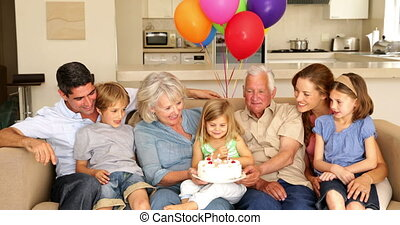 Extended family celebrating little girls birthday on couch...