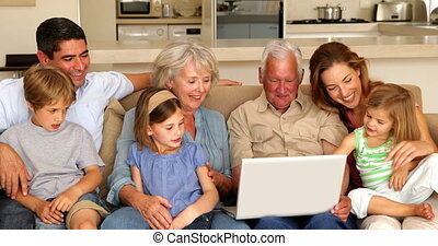 Extended family using laptop together on couch at home in...