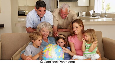 Extended family looking at globe together on couch at home...