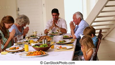 Extended family praying together before dinner at home in...