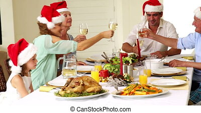 Extended family toasting at christmas dinner at home in the...
