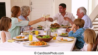 Extended family toasting at dinner at home in the dining...