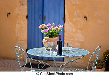 Table for two set with red wine. Provence, France. - Table...