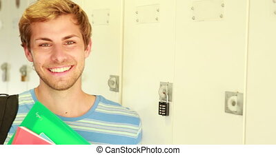 Handsome student leaning on locker looking at camera at the...