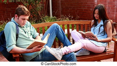 Two students sitting on a bench revising on college campus