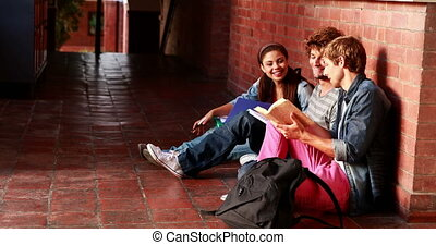 Students sitting against wall revising together at the...