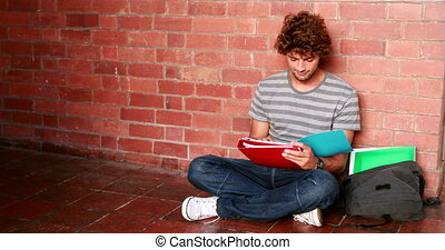 Student sitting against wall reading textbook at the...