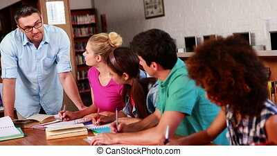Young students revising in the library with their teacher at...
