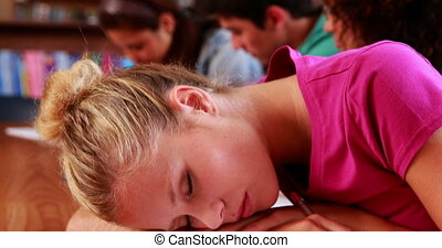 Pretty blonde student sleeping in library at the university