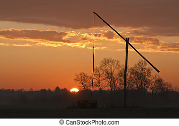 Shadoof at sunrise - Shadoof with orange sky and sun at...