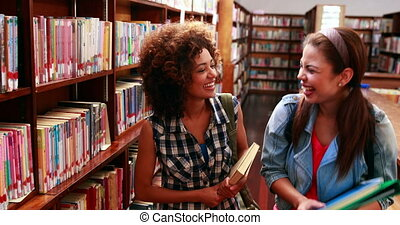 Smiling students laughing and smiling at camera in library...