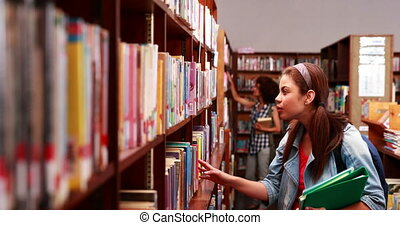 Smiling student picking out a book in library at the...