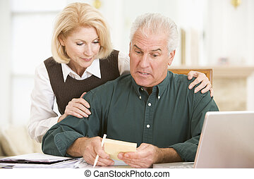 Couple in dining room with laptop and paperwork looking...