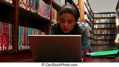 Student lying on floor in library using laptop at the...