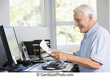 Man in home office with computer and paperwork smiling