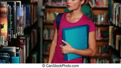 Pretty student picking out a book i - Pretty student picking...