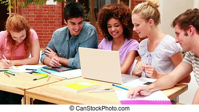 Happy students working together on an assignment at the...