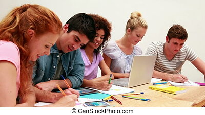 Smiling students working together on an assignment at the...