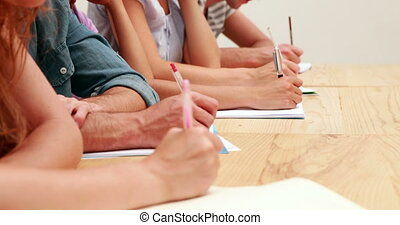 Students sitting in class taking notes at the university