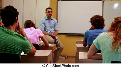 Lecturer sitting and speaking to his students in classroom...