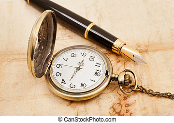 fountain pen and pocketwatch on old parchment