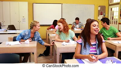 Laughing students throwing paper in classroom at the...