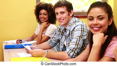 Students sitting in a line smiling