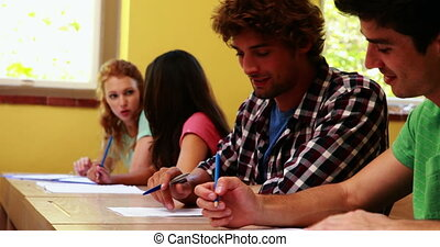 Students sitting in a line writing and chatting in classroom...
