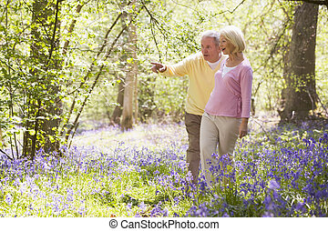Couple walking outdoors pointing and smiling