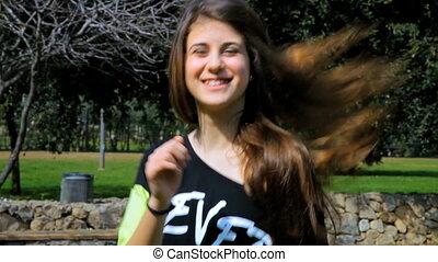 Happy teenager girl dancing in park