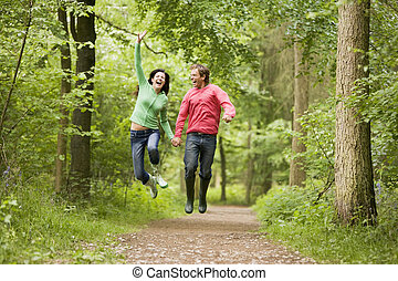 Couple jumping on path holding hands and smiling